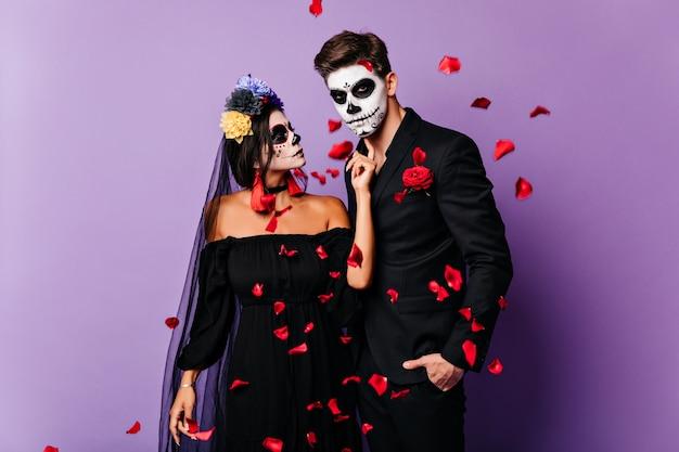 Kochająca Para Wampirów Pozowanie Pod Czerwonym Konfetti. Romantyczne Zombie Odpoczywają Na Imprezie Z Okazji Halloween. Darmowe Zdjęcia