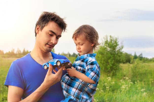 Kochający ojciec z małym synem na zewnątrz bawiąc się samochodem sterowanym radiem Premium Zdjęcia