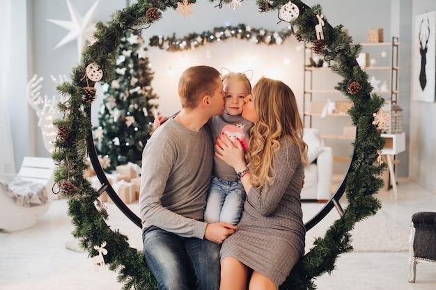 Kochający rodzice całują córkę na boże narodzenie. Premium Zdjęcia