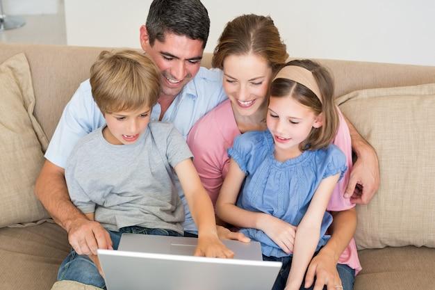 Kochający Rodzinny Używa Laptop Wpólnie Na Kanapie Premium Zdjęcia
