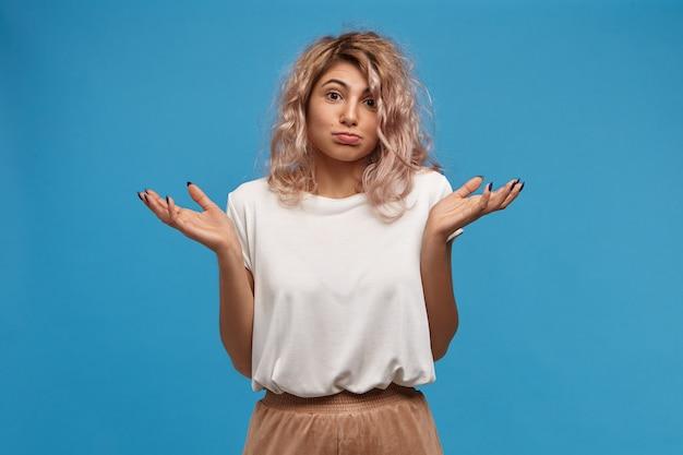 Kogo To Obchodzi, Nie Wiem, Nie Mój Problem. Portret Stylowej Młodej Europejskiej Kobiety Na Sobie Beżową Spódnicę I Białą Górę Wzrusza Ramionami Darmowe Zdjęcia