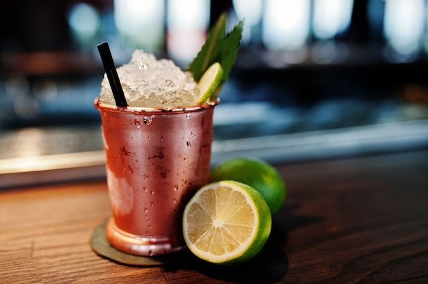 Koktajl alkoholowy z lodem i limonką w brązowej puszce szklanej na stole barowym Premium Zdjęcia