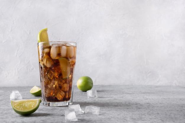 Koktajl Cuba Libre Lub Mrożona Herbata Z Długiej Wyspy Z Romem, Colą, Limonką I Lodem W Szkle Na Szarym Kamiennym Stole. Premium Zdjęcia