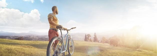 Kolarstwo Mężczyzna Z Rowerem Na Leśnej Drodze W Górach Na Letnim Dniu. Górska Dolina Podczas Wschodu Słońca. Premium Zdjęcia