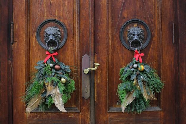 Kołatki Do Drzwi Z Brązowej Głowy Lwa Ozdobione świątecznymi Wieńcami. Wieńce Bożonarodzeniowe Na Drzwiach Drewnianych Premium Zdjęcia