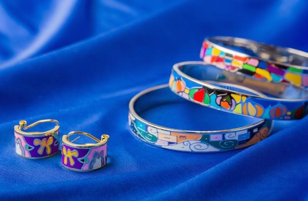Kolczyki I Bransoletka Emaliowane Na Niebieskim Materiale Premium Zdjęcia
