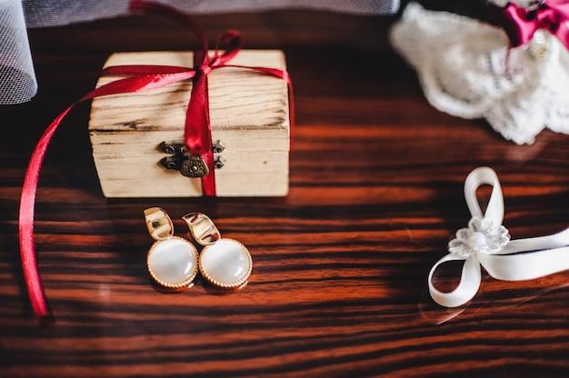 Kolczyki, Pudełko I Podwiązka Na Brązowym Stole Premium Zdjęcia