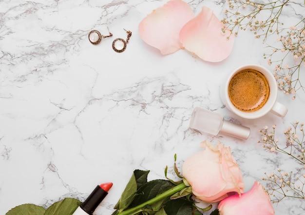 Kolczyki; szminka; róże; lakier do paznokci; filiżanka kawy i oddech dziecka kwiat na teksturowanej tło Darmowe Zdjęcia
