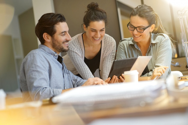Koledzy z warsztatów omawiający pomysły biznesowe w nowoczesnej przestrzeni roboczej Premium Zdjęcia