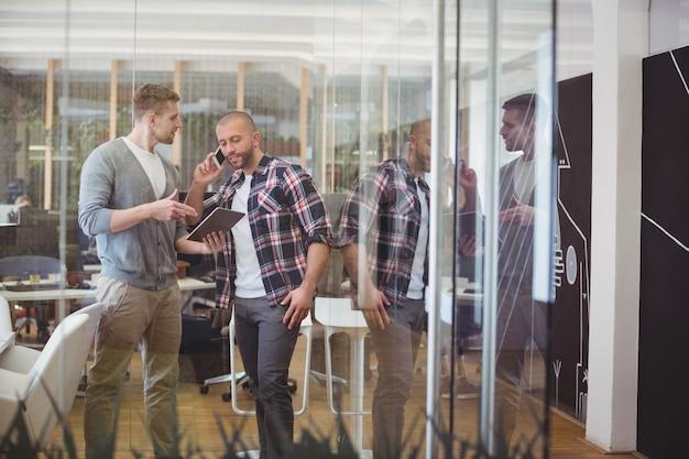 Kolega Dyskutuje Podczas Gdy Biznesmen Opowiada Na Telefonie Premium Zdjęcia