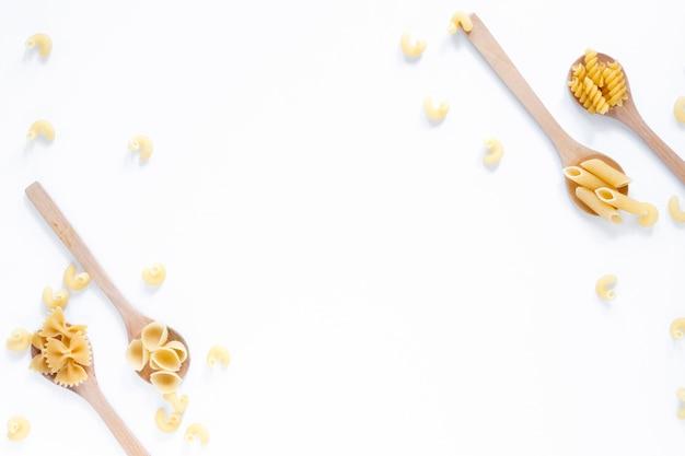 Kolekcja łyżki wypełniać z różnorodnym suchym makaronem nad białym tłem Darmowe Zdjęcia
