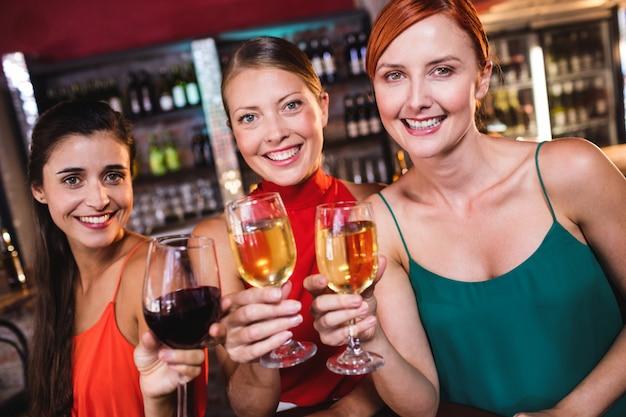 Koleżanki, ciesząc się wina w klubie nocnym Premium Zdjęcia