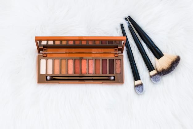Kolorowa Drewniana Eyeshadow Paleta Z Makeup Muśnięciami Na Białym Futerkowym Tle Darmowe Zdjęcia