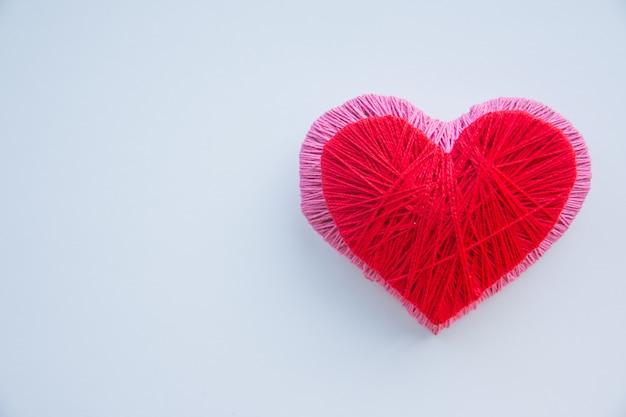 Kolorowa przędzy piłka odizolowywająca. czerwone i różowe serce jak symbol miłości. hobby Premium Zdjęcia