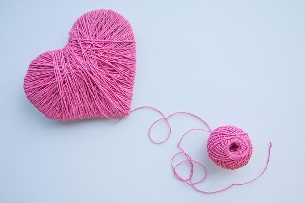 Kolorowa Przędzy Piłka Odizolowywająca Na Bielu. Różowe Serce Jak Symbol Miłości. Koncepcja Hobby. Pocztówka Na Wydarzenie Premium Zdjęcia