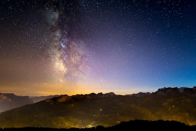 Kolorowa świecąca droga mleczna i gwiaździste niebo nad francuskimi alpami i majestatyczny masyw des ecrins. Premium Zdjęcia
