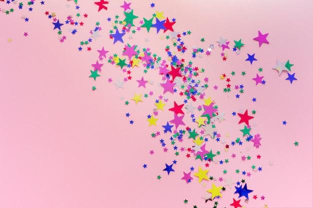 Kolorowe brokat gwiazdy dekoracji, wesołych świąt, szczęśliwego nowego roku na białym tle na różowym tle. konfetti w kształcie gwiazdek Premium Zdjęcia