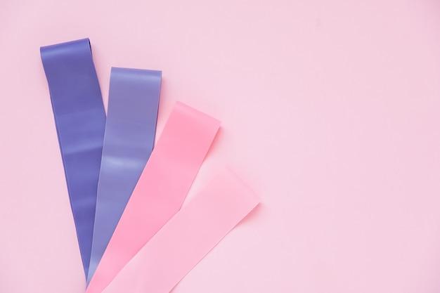 Kolorowe gumy ekspandujące fitness dla kobiet trenujących na różowym tle. proces odchudzania z treningiem cardio. sprzęt do ćwiczeń domowych. utrata masy ciała Premium Zdjęcia