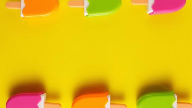 Kolorowe I Różne Plastikowe Zabawki Lody Z Numerami Dla Niemowląt Na żółtym Tle. Premium Zdjęcia