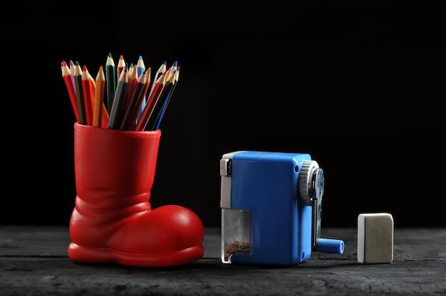 Kolorowe kredki w czerwonych butach, temperówka i gumka Premium Zdjęcia