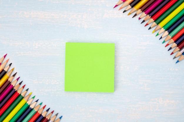Kolorowe kredki w rogu z notatką w niebieskiej ramce Premium Zdjęcia