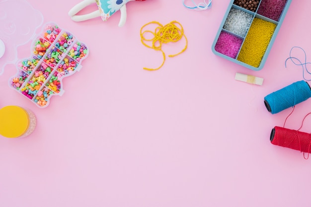 Kolorowe Kulki Przypadku I Szpule Przędzy Na Różowym Tle Darmowe Zdjęcia