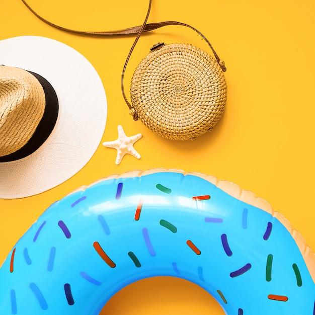 Kolorowe letnie mieszkanie leżało z niebieskim nadmuchiwanym pączkiem, słomkowym kapeluszem, bambusową torbą i rozgwiazdą Premium Zdjęcia