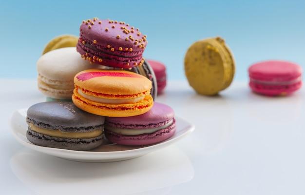 Kolorowe makaroniki. słodkie makaroniki na jasnoniebieskim czasie świątecznym Premium Zdjęcia