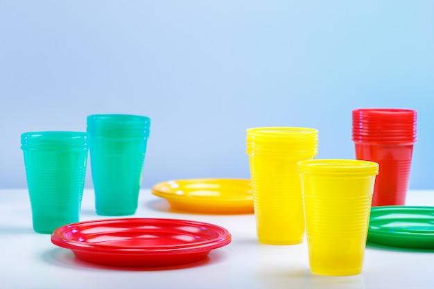 Kolorowe plastikowe naczynia na niebieskim tle z miejsca na kopię. Premium Zdjęcia