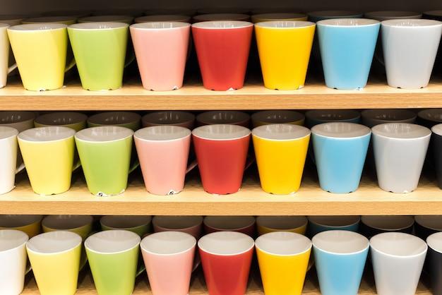 Kolorowe Szklanki Na Półkach W Sklepie. Wszystkie Kolory Tęczy Na Blacie Sklepu Premium Zdjęcia