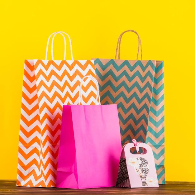 Kolorowe torby na zakupy z projektem na drewnianym stole na żółtym tle Darmowe Zdjęcia