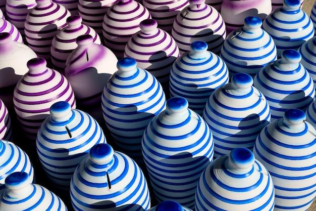 Kolorowe Tradycyjne Ręcznie Wykonane Gliniane Doniczki Z Pomalowanymi W Linii Wokół Zestawione Pod światło Słoneczne I Cień W Tle Premium Zdjęcia