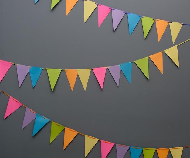 Kolorowe trójkątne flagi firmowe na linie na ciemnoszarej ścianie Premium Zdjęcia