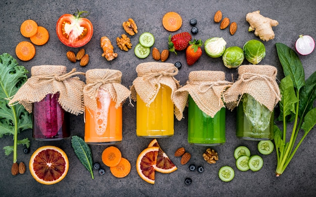 Kolorowe Zdrowe Koktajle I Soki W Butelkach Ze świeżymi Owocami Tropikalnymi I Pożywienie Na Ciemnym Kamieniu Premium Zdjęcia