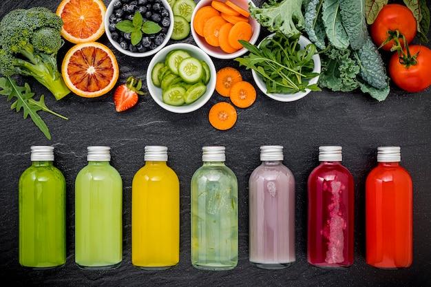 Kolorowe Zdrowe Koktajle I Soki W Butelkach Ze świeżymi Owocami Tropikalnymi Na Ciemnym Tle Kamienia. Premium Zdjęcia