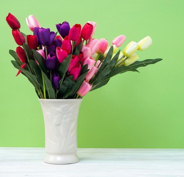Kolorowi tulipany w wazie na bielu stołu ściany zieleni tle Premium Zdjęcia
