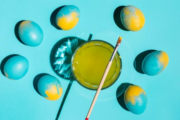 Kolorowi wielkanocni jajka z farby muśnięciem i szkło woda na stole Darmowe Zdjęcia