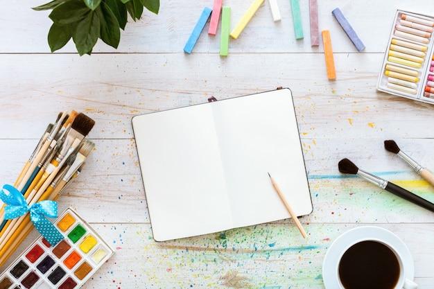Kolorowy Kreatywny Stół Z Pustego Notatnika Na Szkice I Farby, Widok Z Góry Premium Zdjęcia