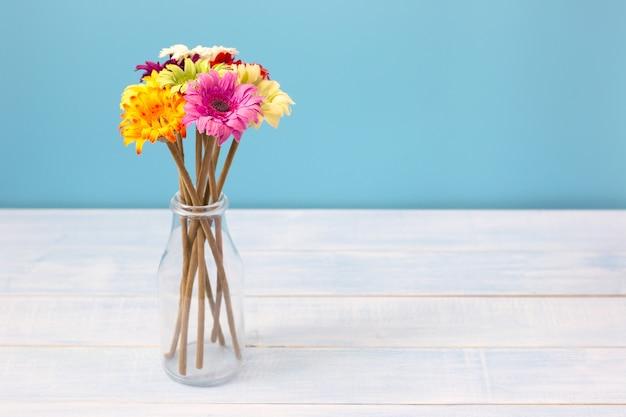 Kolorowy Kwiatu Bukiet W Jasnej Butelce Na Bławym Stole Przed Błękitną ścianą. Zobacz Z Miejsca Na Kopię Premium Zdjęcia