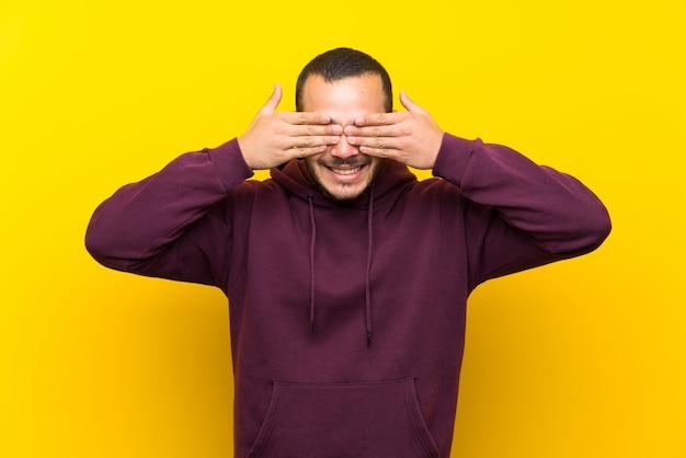 Kolumbijski mężczyzna z bluzą nad żółtymi ścianami zakrywającymi oczami rękami Premium Zdjęcia