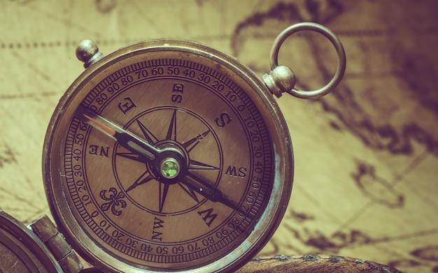 Kompas Z Pokrywą Pokrywy Na Starej Mapie świata Premium Zdjęcia