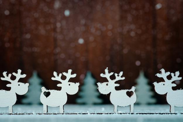 Kompozycja Białych Reniferów I Choinek Na Drewnianych. świąteczny Wystrój Premium Zdjęcia