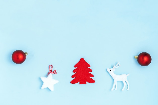Kompozycja noworoczna i świąteczna. rama z czerwonych kulek, białych gwiazd, chrismas, jelenia i iskier na pastelowym niebieskim tle papieru. widok z góry, leżał płasko, miejsce Premium Zdjęcia
