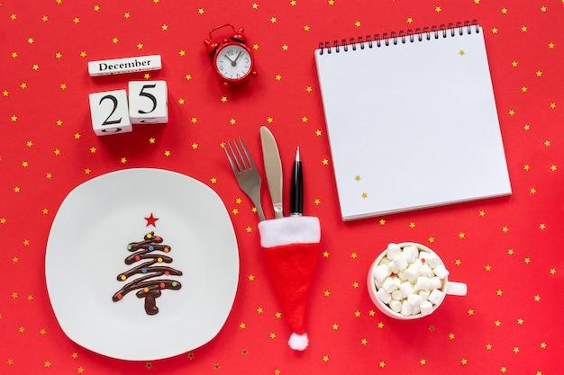 Kompozycja świąteczna kalendarz 25 grudnia słodka czekoladowa choinka na talerzu, sztućce w czapce mikołaja filiżanka kakao Premium Zdjęcia
