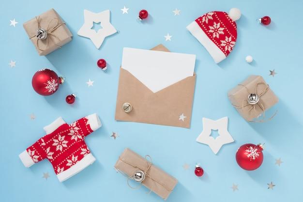 Kompozycja świąteczna lub zimowa z kopertowymi i czerwonymi dekoracjami na pastelowym niebieskim tle. koncepcja nowego roku. Premium Zdjęcia