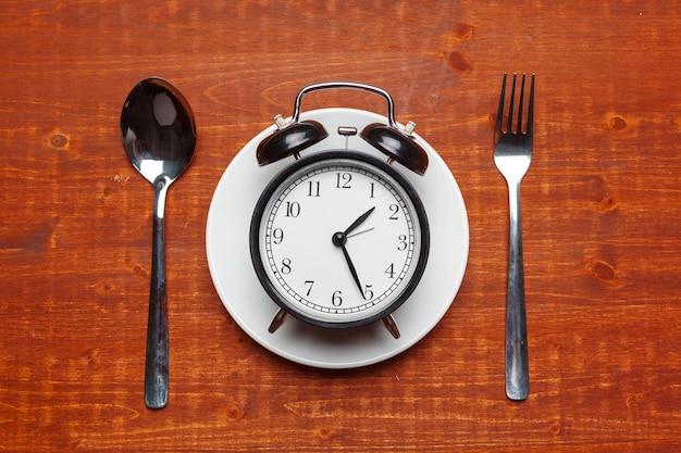 Kompozycja z budzikiem, talerzem i przyborami kuchennymi Premium Zdjęcia