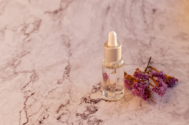 Kompozycja Z Fioletowymi Kwiatami Limonium, Naturalnymi Kosmetykami Na Marmurowym Tle. Szklana Butelka I Różne Organiczne Zioła. Premium Zdjęcia