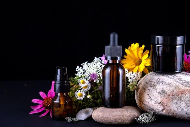 Kompozycja Ze Szklanymi Butelkami Na Kamiennym Cokole Z Mchami I Kwiatami Premium Zdjęcia