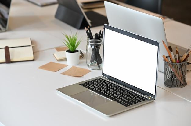 Komputer macbook z pustym ekranem na kreatywnym pokoju konferencyjnym. Premium Zdjęcia