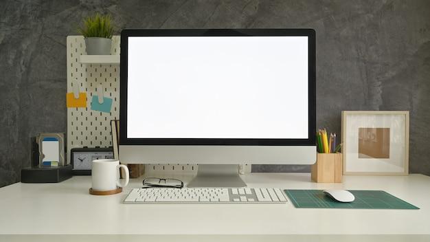 Komputer roboczy, ołówek, tablica z kawą na stole ze ścianą strychu. Premium Zdjęcia
